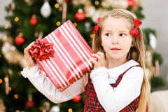 Christmas: Girl Shakes Present To Hear What Is Inside Royalty Free Stock Image