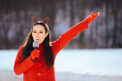 Christmas Girl Singing Carols Outdoors in Wintertime. Funny woman with microphone caroling outside on holiday season royalty free stock image