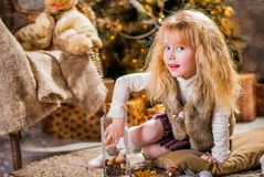 Christmas. Girl  sitting on the floor in front of the Christmas tree Royalty Free Stock Images