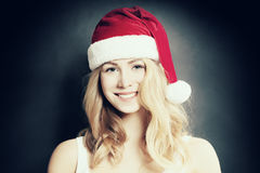 Christmas Girl. Smiling Woman in Santa Hat on Background. Christmas Girl. Smiling Woman in Santa Hat on Dark Background Royalty Free Stock Image