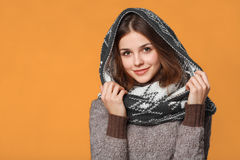 Christmas girl wearing knitted wear scarf. Young beautiful smiling girl, winter concept, isolated over orange background Royalty Free Stock Photo