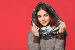 Christmas girl wearing knitted wear scarf. Young beautiful smiling girl, winter concept, isolated over red background Stock Photo