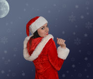 Christmas girl wearing a Santa hat Stock Images