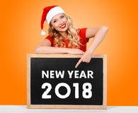 Christmas girl, winter concept. Beautiful blonde girl in red dress and Santa Claus hat points to a new year`s date Stock Photo