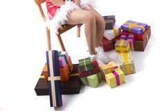 Christmas girl on a wooden chair and gifts. On white background Royalty Free Stock Photos