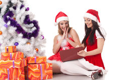 Christmas girlfriends with laptop. Royalty Free Stock Photography