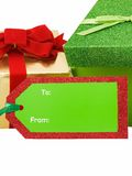 Christmas Giving. Christmas gift tag in front of presents isolated on white Royalty Free Stock Photo