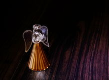 Christmas - a glass angel on a dark surface. A little glass angel stands on a dark wooden surface stock photo