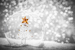 Christmas glass ball with crystal tree inside in snow. Glitter background Stock Images