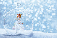 Christmas glass ball with crystal tree inside in snow. Glitter background stock photo