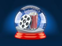 Christmas glass ball with film reel and popcorn. On blue background Royalty Free Stock Photos