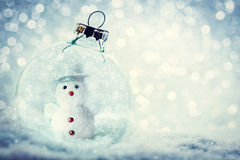Christmas glass ball with snowman inside. Snow and glitter. Christmas glass ball with snowman inside. Snowy, glitter background royalty free stock image