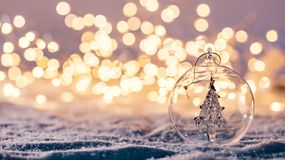 Christmas glass ball with tree in it on winter background. royalty free stock images