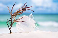 Christmas glass ball on white sand beach with seascape backgrou Stock Image
