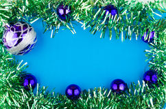 Christmas glass balls and tinsel in form of frame. With blue background Stock Photography