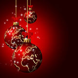 Christmas glass balls with world pattern over dark  background Stock Images