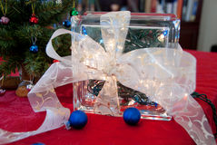 Christmas Glass Block Decoration. A glass block filled with a string of Christmas lights has a beautiful white bow tied around it. This decoration sits with Stock Image