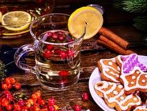 Christmas glass latte mug with lemon and cookies on plate. Christmas treats. Christmas glass latte mug and Christmas multicolored cookies on plate with fir royalty free stock photography