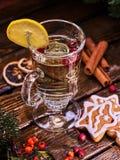 Christmas glass latte mug with lemon and cookies on plate . Christmas glass latte mug and Christmas multicolored cookies on plate with fir branches. Mag stock photo