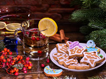 Christmas glass latte mug with lemon and cookies on plate . Christmas treats. Christmas glass latte mug and Christmas multicolored cookies on plate with fir royalty free stock image