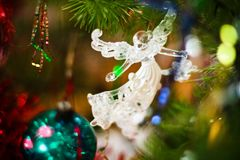Christmas glass toy in the form of an angel on the Christmas tree. Among the balls and lights royalty free stock image