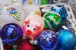 Christmas glass toy pink piggy among colorful balloons stock photos