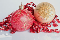 Christmas Glitter. Two Christmas Baubles nestled in red curling ribbon Stock Photo