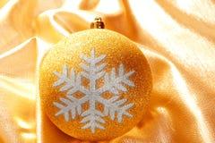 Christmas glitter golden snowflake bauble. Christmas glitter snowflake bauble on golden fabric background Stock Photo
