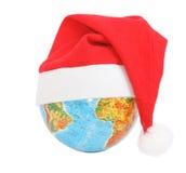 Christmas globe. Globe wearing a Santa Claus hat Stock Photos