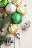 Christmas Globes and Cones. Golden and Green Festive Christmas Globes with Cones on Painted Wood Royalty Free Stock Photography