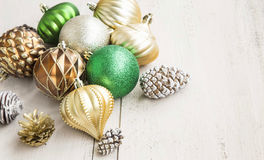 Christmas Globes and Cones. Golden and Green Festive Christmas Globes with Cones on Painted Wood Royalty Free Stock Photos