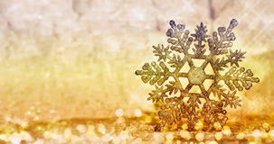 Christmas glowing golden snowflake on blurred background. Stock Photos