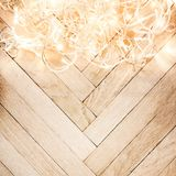 Christmas glowing  lights garland on a old antique wooden parque. T floor, sparkling  garland. Christmas background with festive decoration Stock Photos