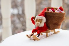 Christmas gnome sits on wooden sled with bag of gifts behind him. Real snow background. Vintage toy Royalty Free Stock Photography