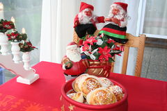 Christmas gnomes and buns with saffron. Smiling Christmas gnomes, one boy and one girl, are sitting on chair during Christmas time together with saffron buns in Stock Photography