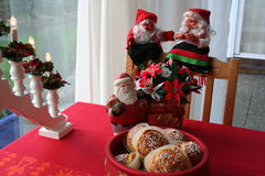 Christmas gnomes and buns with saffron. Smiling Christmas gnomes, one boy and one girl, are sitting on chair during Christmas time together with saffron buns in Stock Photos