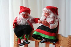 Christmas gnomes. Smiling Christmas gnomes, one boy and one girl, are sitting on chair during Christmas time Stock Photo