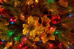 Christmas Gold. Christmas tree with golden poinsettia ornament royalty free stock image