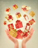 Christmas gold background with gift boxes and hands. Stock Image