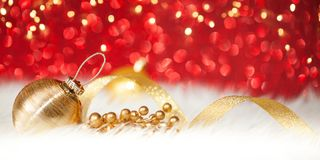 Christmas gold ball on red glitter background. Christmas gold ball and tape on red glitter background stock photography