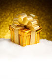 Christmas gold gift box with balls and decoration on snow Royalty Free Stock Image