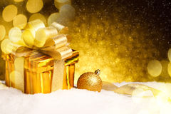 Christmas gold gift box with balls and decoration on snow Stock Photography