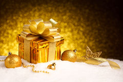 Christmas gold gift box with balls and star on snow. New Year Decorations royalty free stock photo