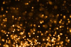 Christmas gold gradient sparkle glitter dust particles from top. On black background with bokeh flowing movement, golden holiday happy new year and valentine stock image