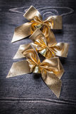 Christmas gold-shining bows with bells on wooden Royalty Free Stock Photo
