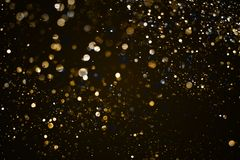 Christmas gold sparkle glitter explosion dust particles backgrou. Nd with bokeh, gold holiday happy new year and valentine day concept Stock Photos