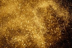 Christmas gold sparkle glitter explosion dust particles background with bokeh, gold holiday happy new year and valentine day. Concept royalty free stock image