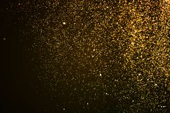 Christmas gold sparkle glitter explosion dust particles backgrou. Nd with bokeh, gold holiday happy new year and valentine day concept Royalty Free Stock Photos