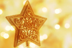 Christmas gold star. Holiday star decoration with golden lights in the background Stock Photos