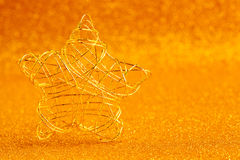 Christmas gold wire star on golden glitter Royalty Free Stock Image